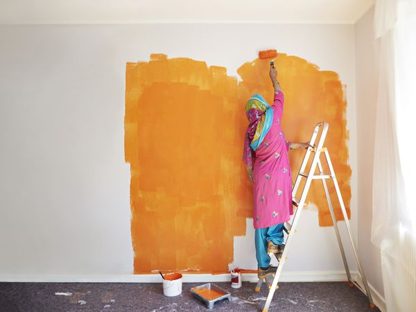 Rear view of senior woman painting wall with orange color while standing on ladder