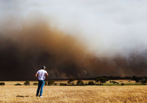 Man looking at a dark cloud of wildfire smoke