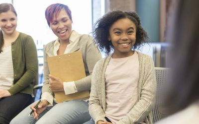 Young girl talks with school counselor