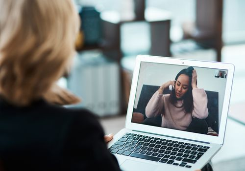 Shot of a young woman having a counselling session with a psychologist using a video conferencing tool