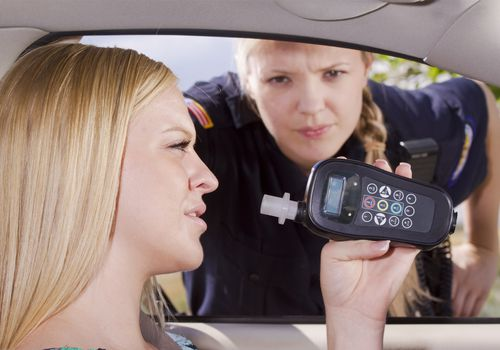 Woman holding breathalyzer machine up while female police officer leans in her car window