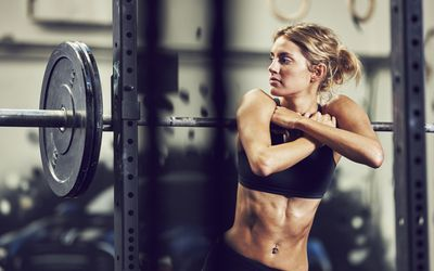 woman leaning on barbell on weight rack