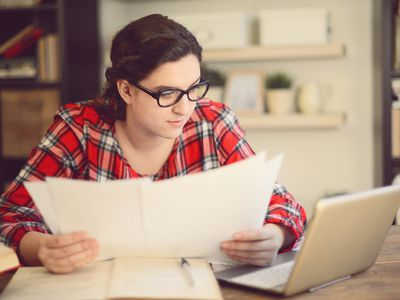 young woman looking at papers next to laptop