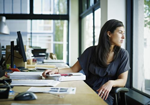 Businesswoman sitting in office looking out