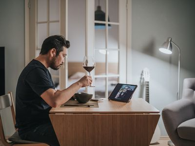 Man having a glass of wine and talking to a friend online.