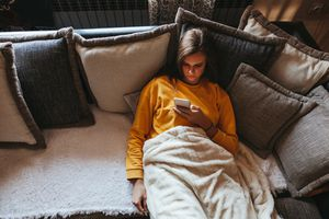 Woman lying on couch scrolling on her smartphone