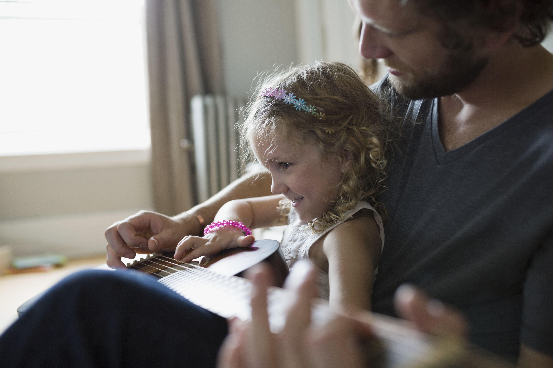 Father teaching daughter playing guitar