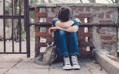 Depressed teenage girl covering face while sitting on the ground