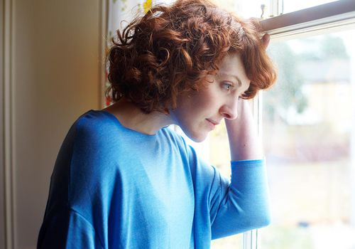 Girl looking out of window of house in suburban street