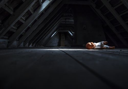 Doll laying in a dark empty attic
