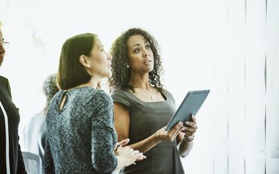 Two businesswomen look up at screen. One is holding an iPad.