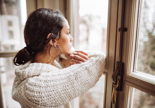 Pensive woman looking out of a window.