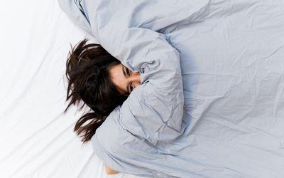 woman lying under a big blanket