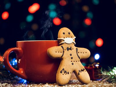 Gingerbread man leaning against coffee cup with COVID-19 mask