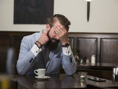 Tired man in suit covering eyes with hand