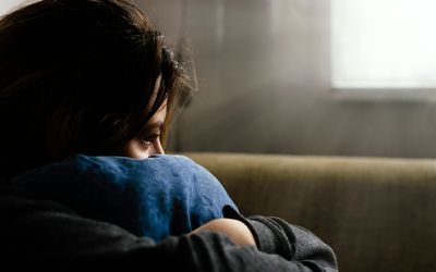 sad teenager hugging a pillow while sitting on the couch