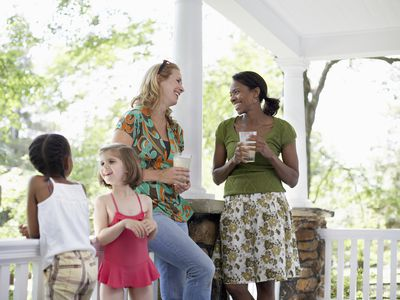 two female neighbors talking on porch while their children play