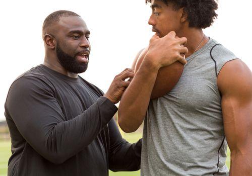 A Black football coach trains a young Black athlete