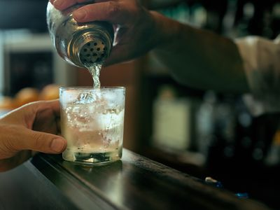 Close-up of bartender hand pouring cocktail