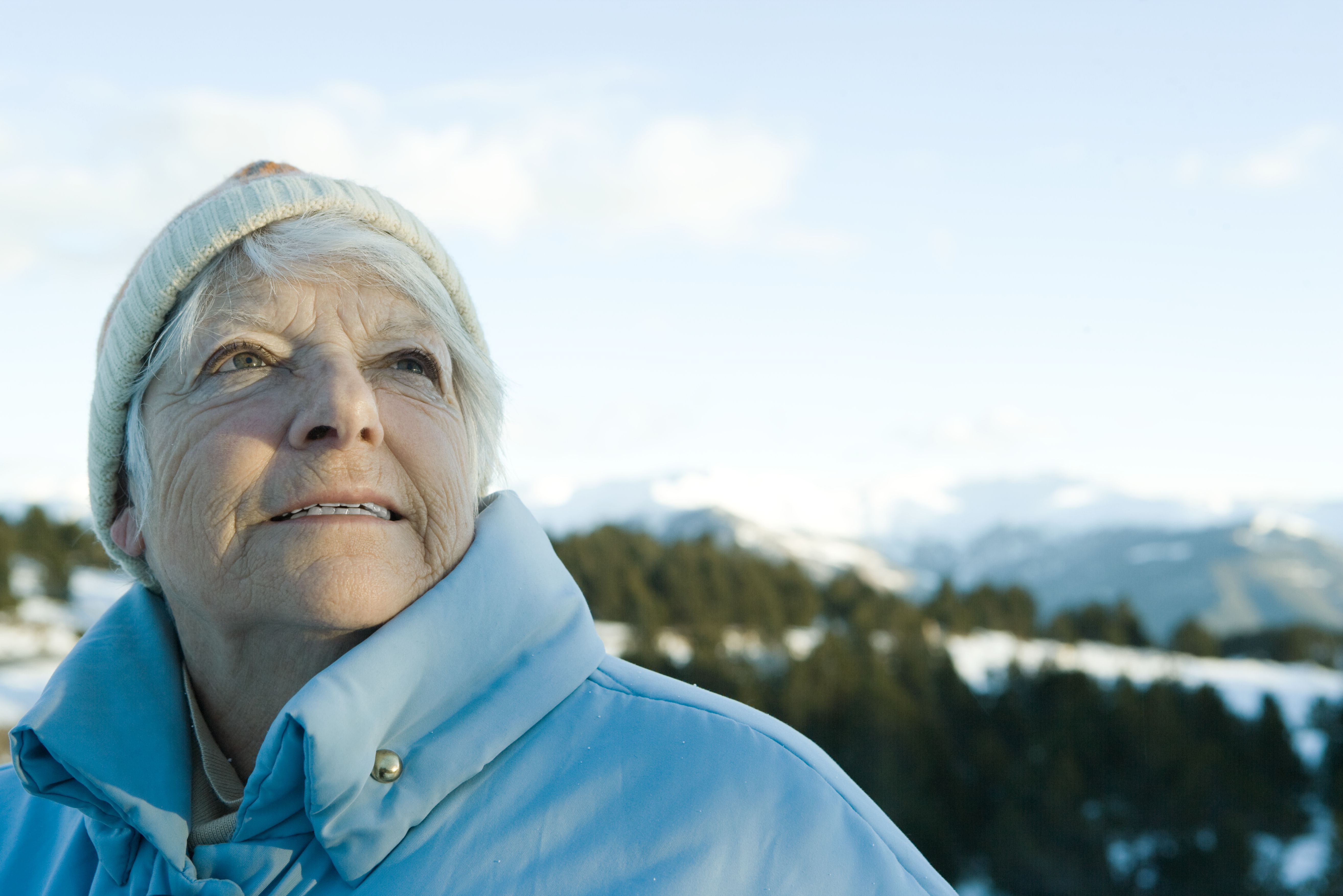 Senior woman standing in snowy landscape, looking up