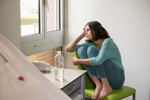 Sad woman sitting on the chair in a hospital ward and looking out window