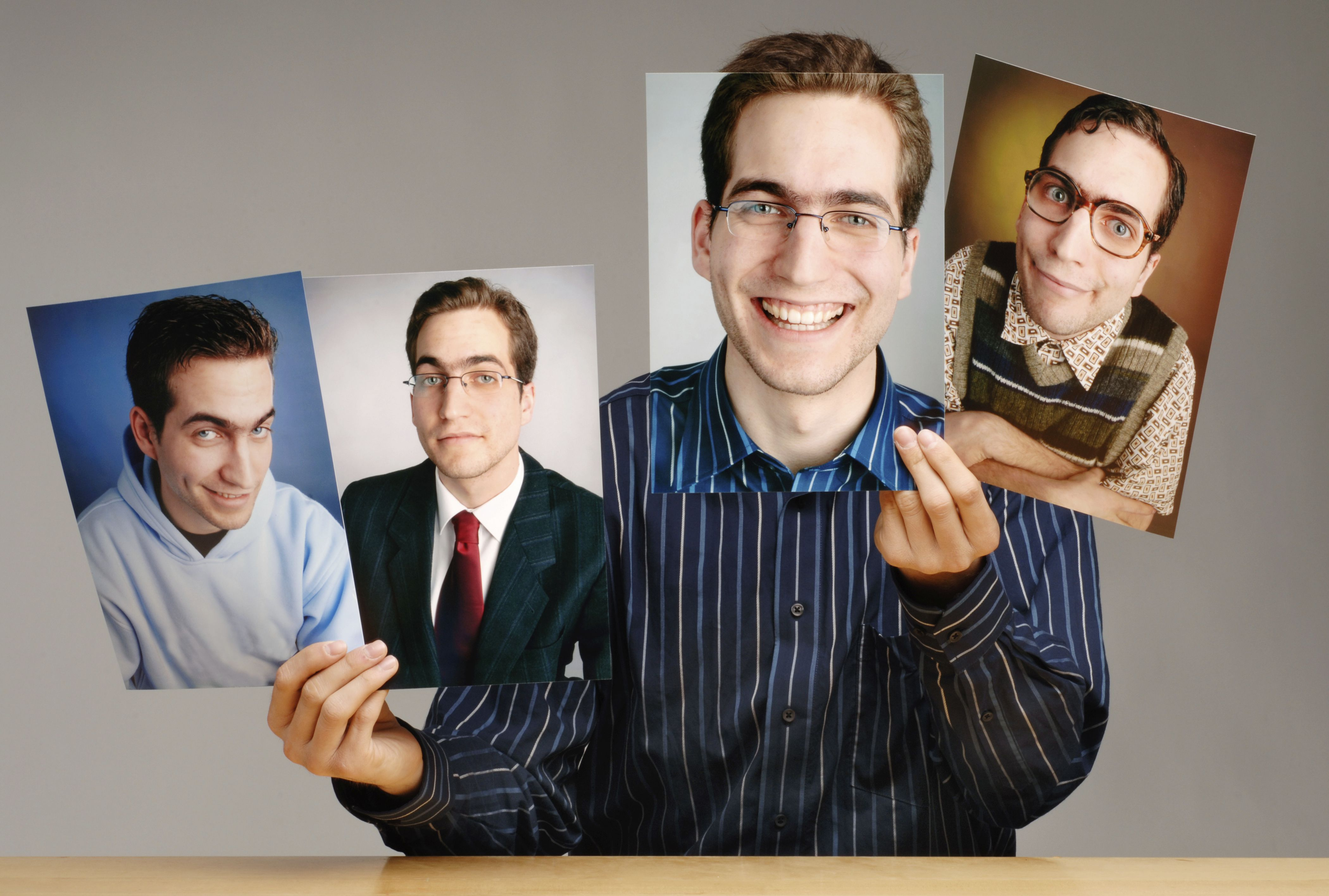 Man holding up photos of himself with different facial expressions