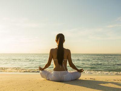 Woman meditating on a beach