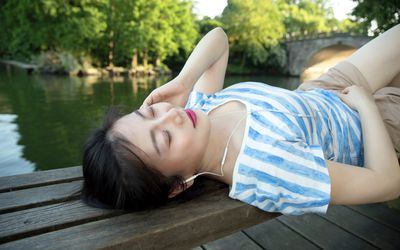 Young asian woman lying on pier above lake,enjoying listening to music