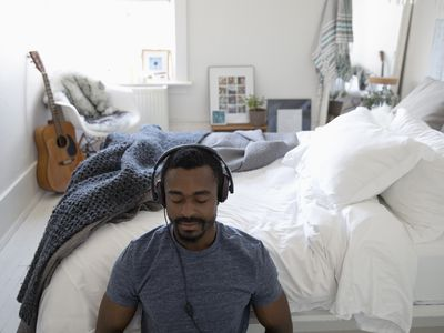man meditating with headphones on next to his bed