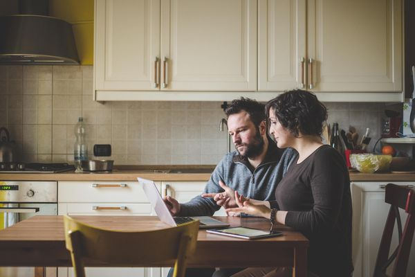 Couple sitting at table, using laptop