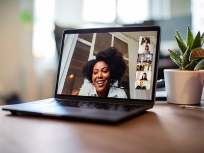 Laptop on table showing woman on smiling on video conference with five others