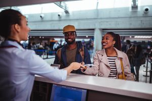 A happy couple hands their passport to an airport worker.