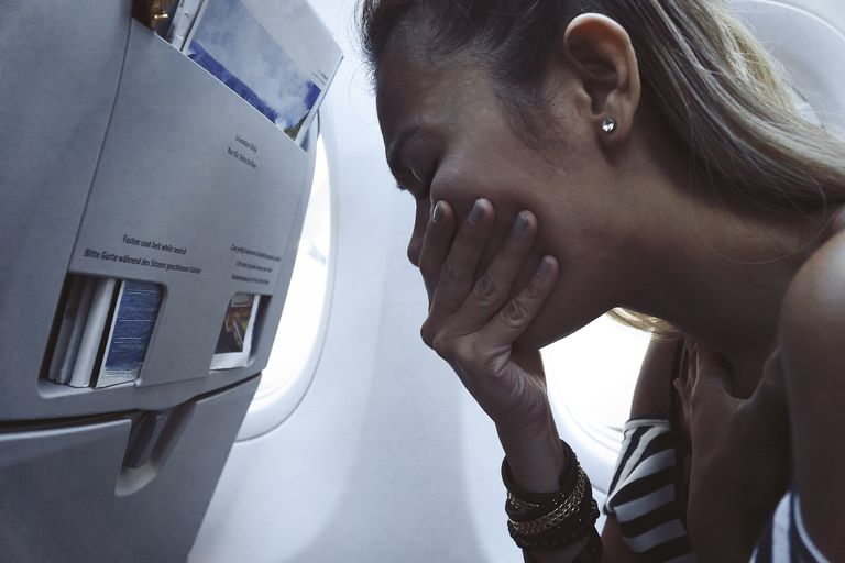 Distressed woman covering her mouth, leaning forward in an airplane seat