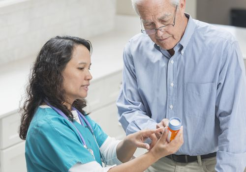 Home nurse helping senior man with medication