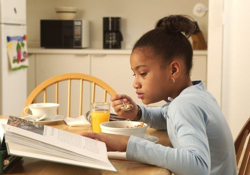 Girl sitting at breakfast table reading a book