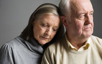 Older man and woman looking sad