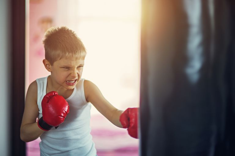 Little boy hitting hard punching bag
