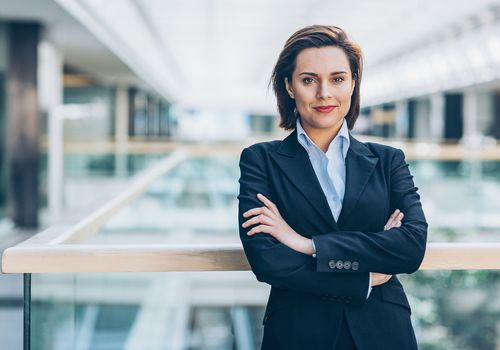 confident businesswoman smiling with her arms folded
