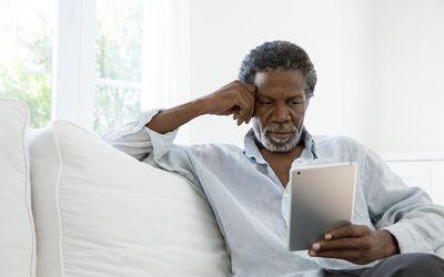 Senior man using digital tablet on sofa