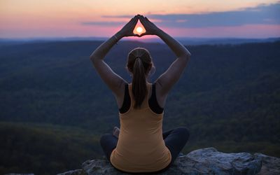 Woman sitting outside in lotus position with the setting sun framed with her hands
