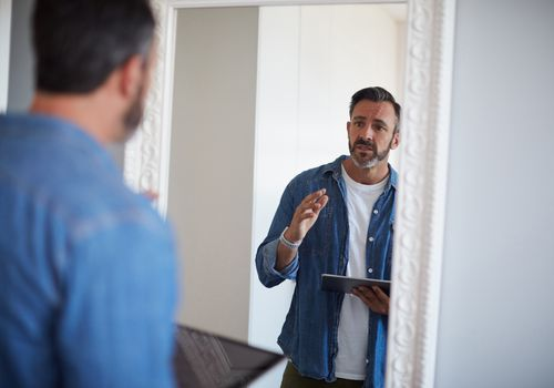 Cropped shot of an attractive mature man having a rehearsal in the mirror while holding a digital tablet