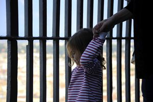 little girl holding her father's hand in prison