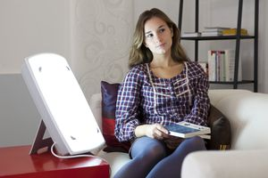 A woman sitting next to a light therapy box