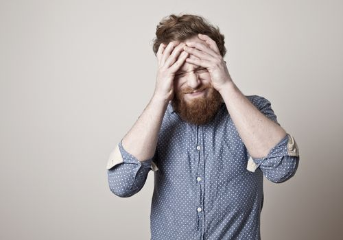 Bearded man with pained face grabbing his head with his hands