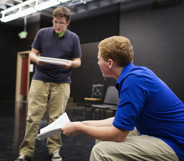 Students reading scripts in high school drama class