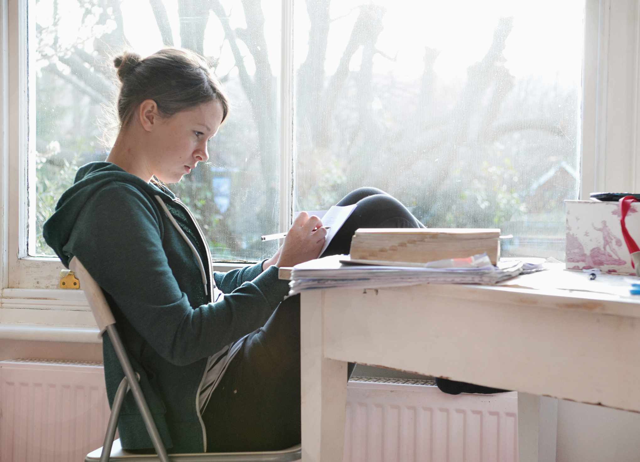 Girl studying and writing notes next to window