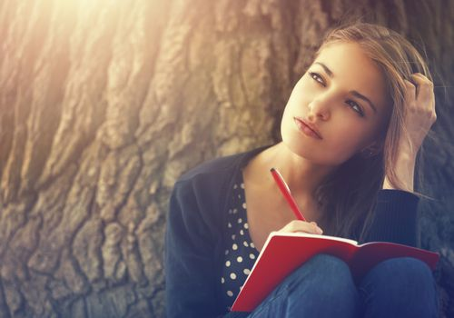young woman deep in thought writing in journal against tree