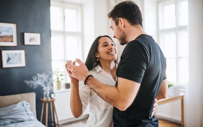 Affectionate young couple in love dancing at home, having fun