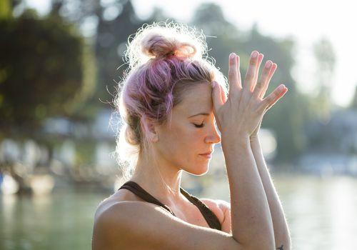 Woman with dyed hair meditating at a lake