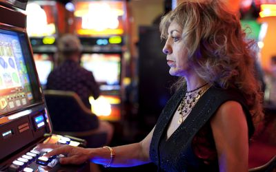 middle-aged woman gambling on electronic casino game